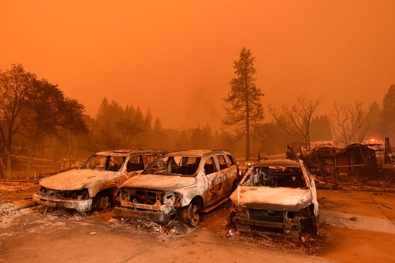 Burned vehicles in a parking lot engulfed in a smoky haze.