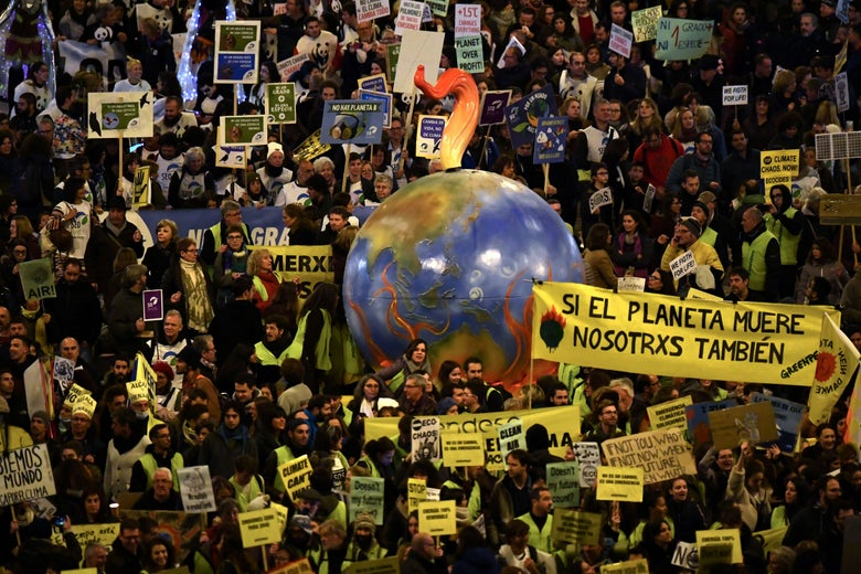 A mass climate protest featuring signs in various languages and a balloon resembling Earth
