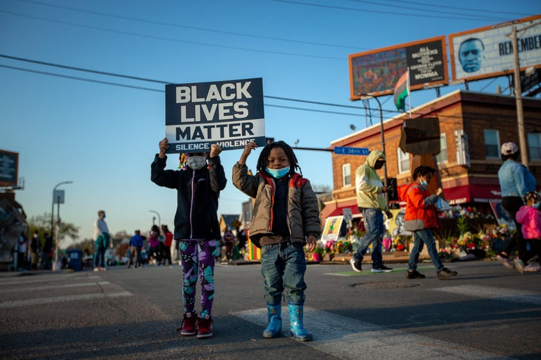 Two kids hold up a Black Lives Matter sign in George Floyd Square.