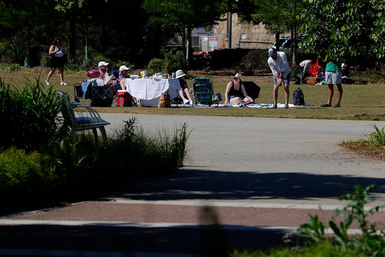 A group of people sit and have a picnic in the park