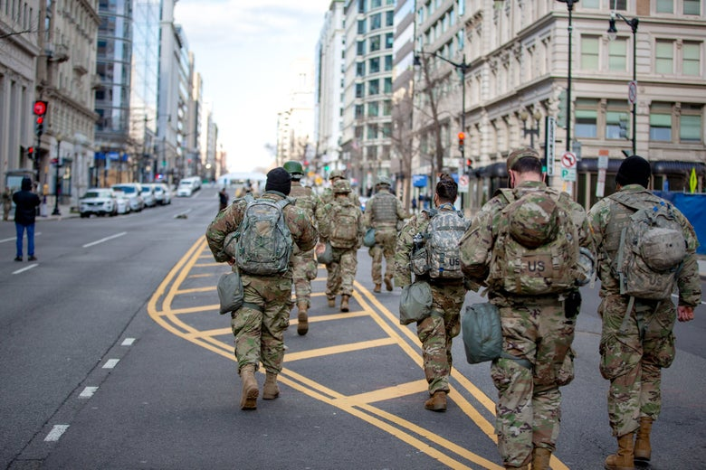 National Guard members in camo walk away from the camera in the middle of an empty street