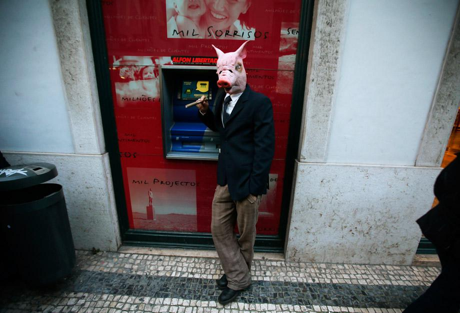 A demonstrator wearing a mask of a pig smokes during a march against government austerity policies in central Lisbon March 2, 2013.