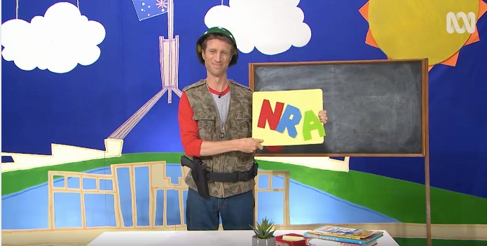 Australian musical comedian Sammy J holds up the most important letters of the alphabet: N, R, and A.