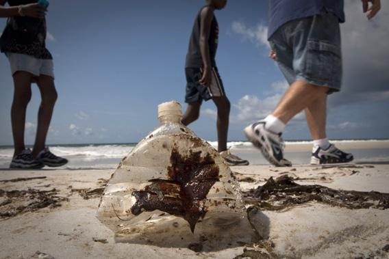 Beachgoers walk past a bottle coated with oil from the Deepwater Horizon oil spill in Pensacola Beach, Florida