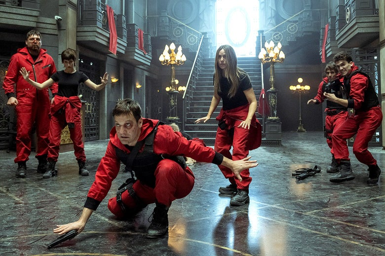 Five thieves in red jumpsuits spread out across the inside of a bank.