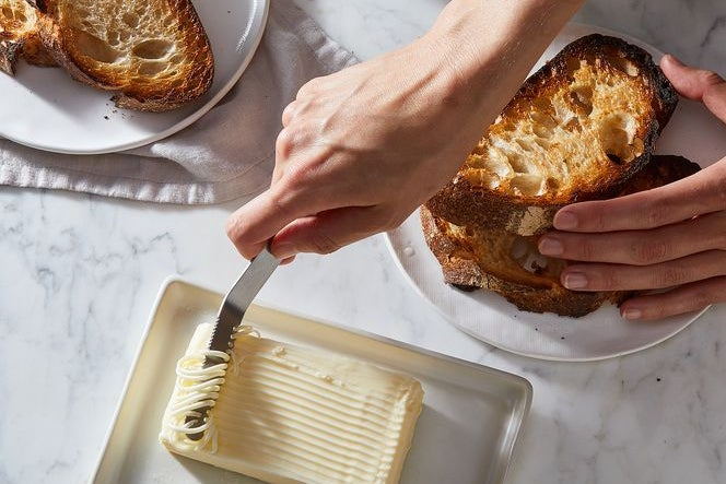 Toasted bread with a knife cutting butter.
