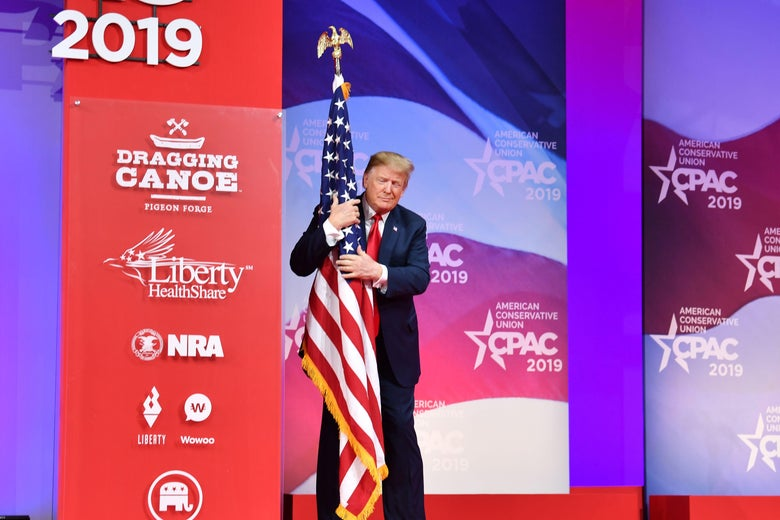 President Donald Trump hugs the U.S. flag as he arrives to speak at the annual Conservative Political Action Conference (CPAC) in National Harbor, Maryland, on March 2, 2019.