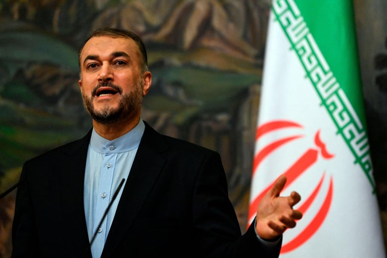 Hossein Amir-Abdollahian gestures as he speaks at a press conference with an Iranian flag behind him