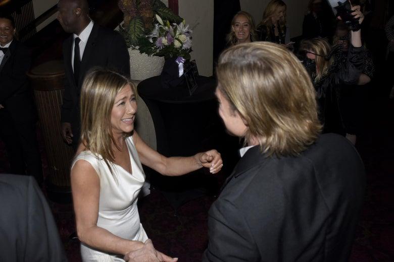 A high angle shot of Jennifer Aniston smiling at Brad Pitt.