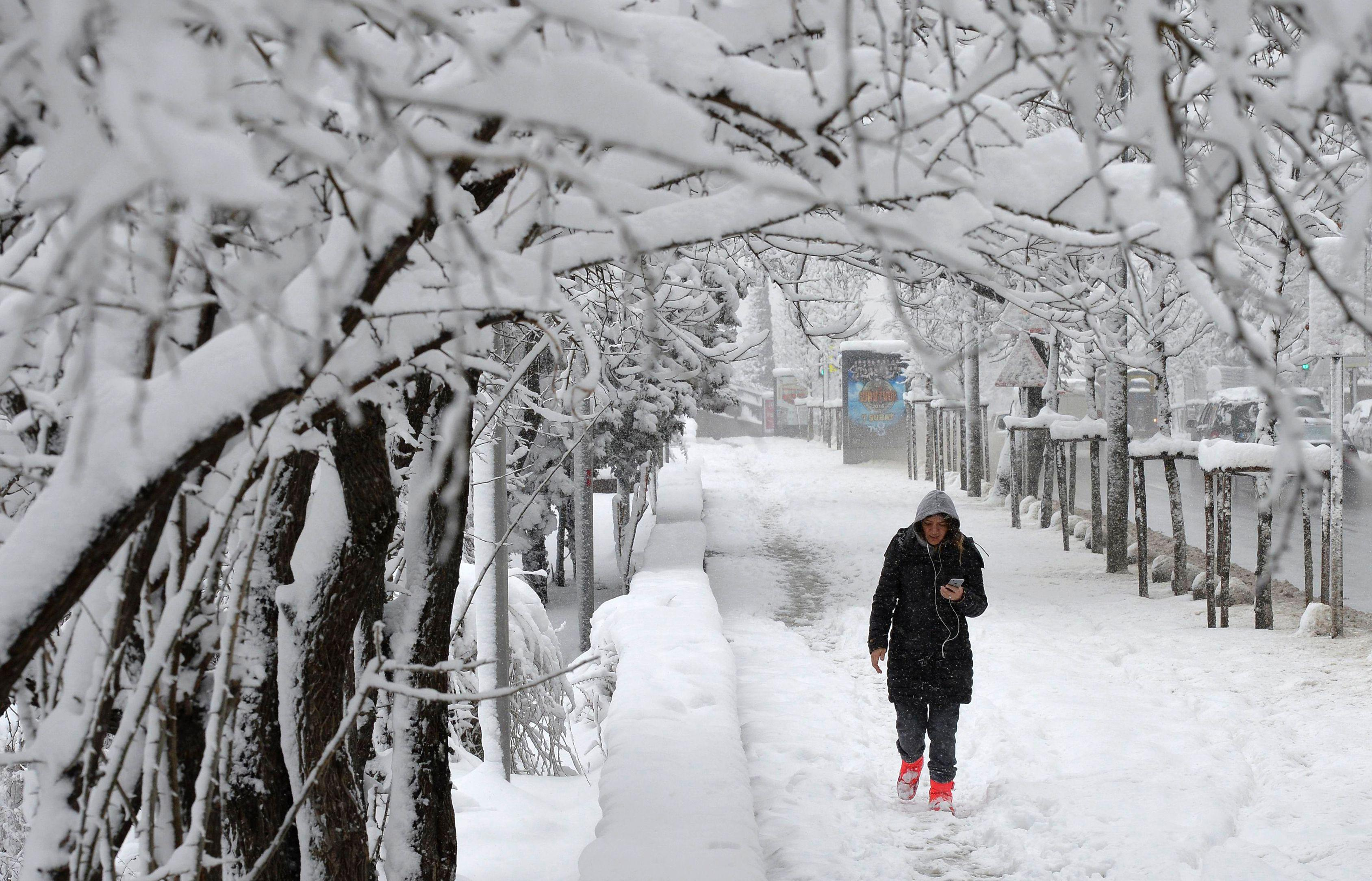 A woman talks on the phone as she walks under the snow in Ankara on February 6, 2016. / AFP / ADEM ALTAN        (Photo credit should read ADEM ALTAN/AFP/Getty Images)