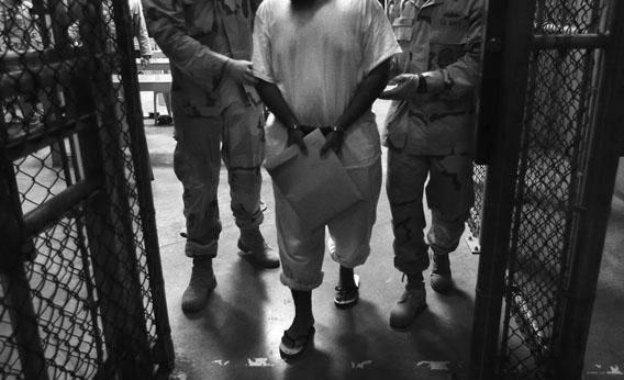 "In this file photo, U.S. guards escort an unnamed detainee after a ""life skills"" class for prisoners at Guantánamo Bay in 2010."