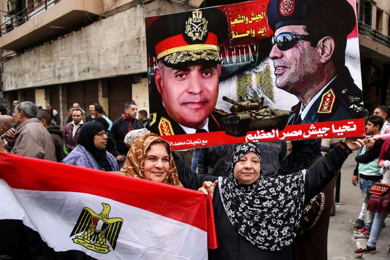 Egyptian women hold their national flag and a poster bearing portraits of President Abdel Fattah al-Sisi and Defense Minister Sedki Sobhi in Cairo's Tahrir Square on Jan. 25, 2017.