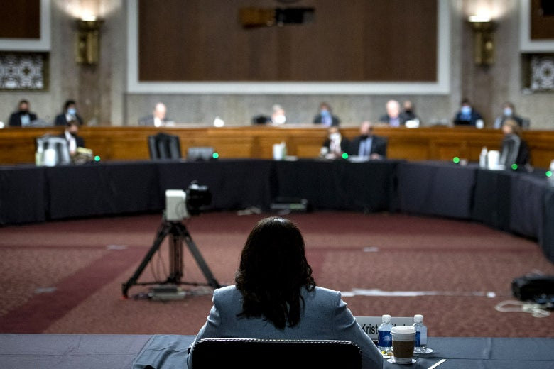 Kristen Clarke's back is seen as she sits a table inside a hearing room. Ahead in the distance, senators can be seen sitting at desks.