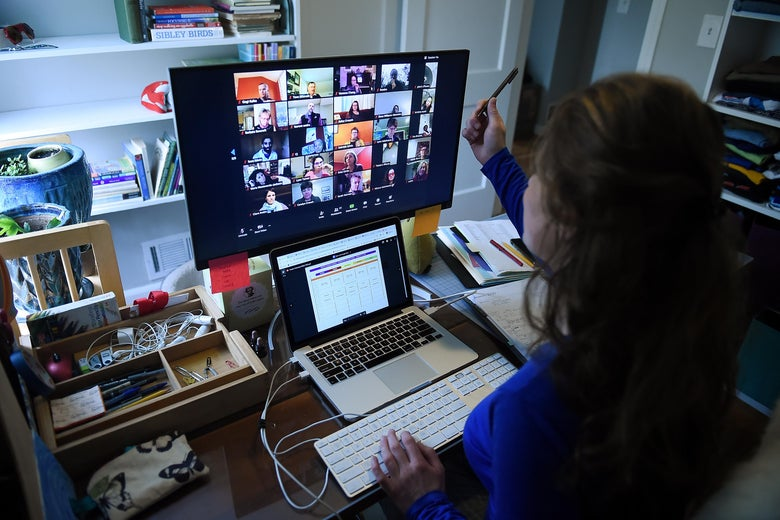 A woman looks at a screen—the back of her head is visible. She has her laptop before her and a monitor featuring Zoom, with windows of people staring back at her.