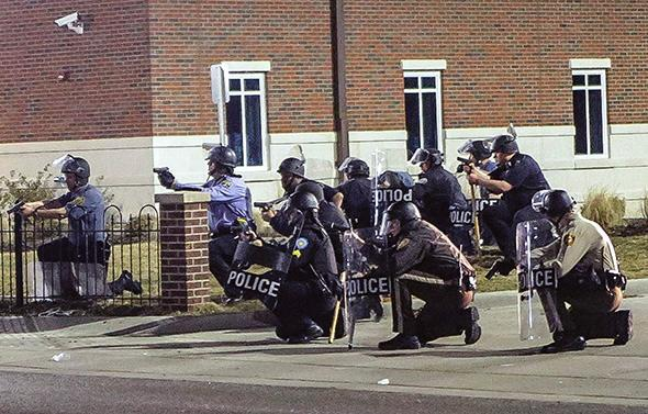 Police officers respond to a fellow officer hit by gunfire outside the Ferguson police headquarters in Ferguson, Missouri, on March 12, 2015