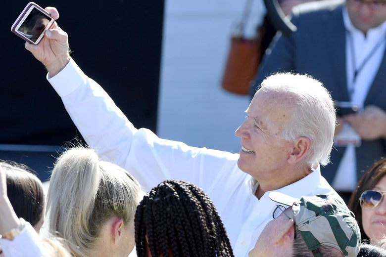Biden raises his arm, holding a phone, to take a selfie in a crowd of people.