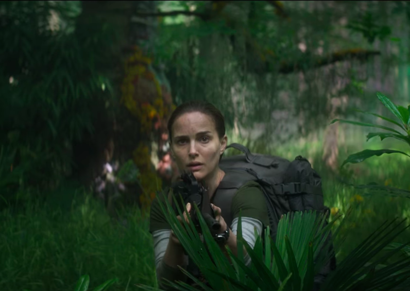 Natalie Portman stands amid foliage holding a machine gun