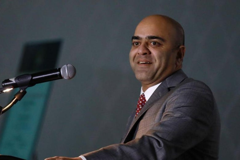 Zahid Quraishi smiles as he stands at a podium