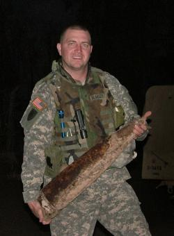 "Staff Sgt. Richard ""Doc"" Blakley with an artillery shell mine he discovered"