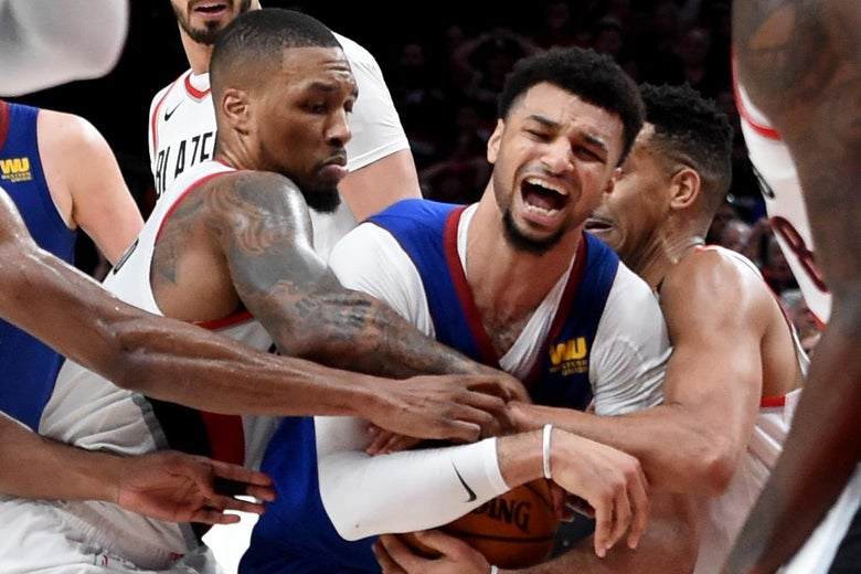 Damian Lillard and C.J. McCollum of the Portland Trail Blazers tie up Jamal Murray of the Denver Nuggets during the third overtime of Game 3 of the Western Conference Semifinals at Moda Center in Portland, Oregon.