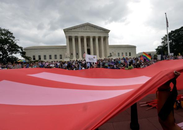 People wave a giant equality flag in celebration outside the Supreme Court in Washington, D.C. on June 26, 2015, after its historic decision on gay marriage.