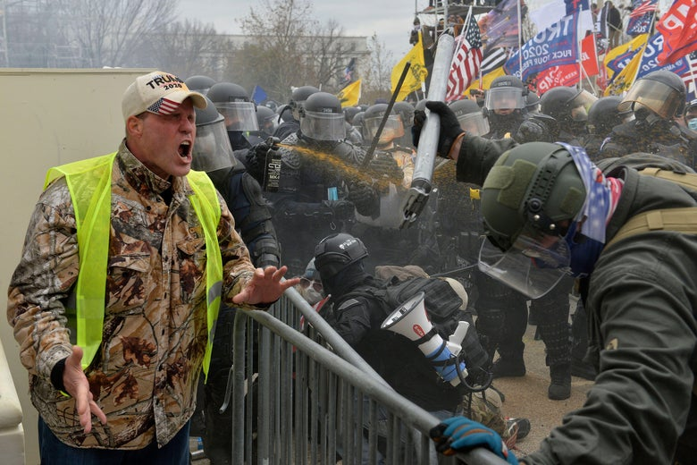 Guy wearing camo and a MAGA hat screaming at police in military-style gear, with Trump flags looming in the background outside the Capitol
