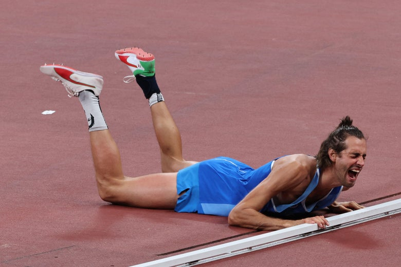 A tall, lanky high jumper lies belly-down on the ground, his legs raised behind him, screaming.