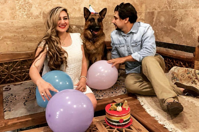 Mahdis sits with her husband and a German shepherd wearing a party hat. It is a scene of celebration: All are smiling with balloons around them and a cake on the table in front of them.