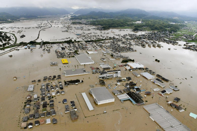An aerial view of widespread flooding in Kurashiki, Japan, showing submerged houses and facilities.