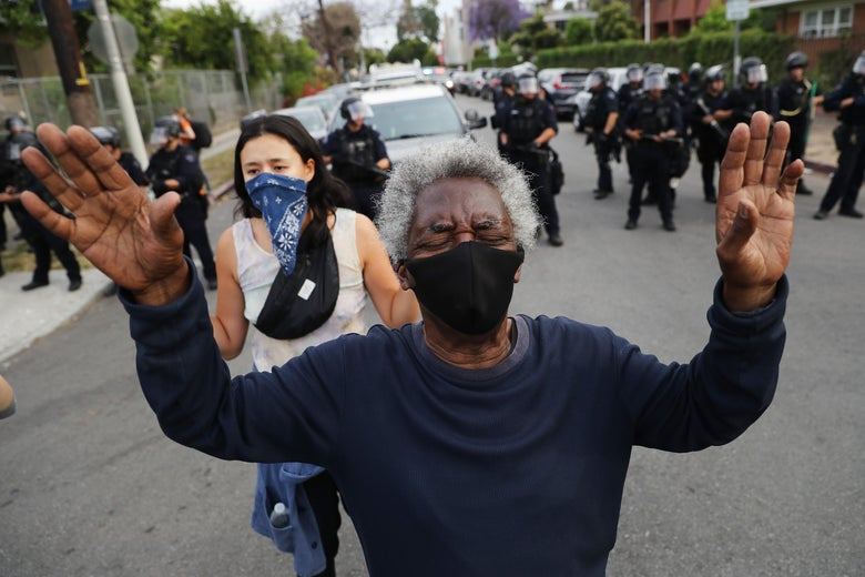 Person with hands raised and back to a line of militarized police