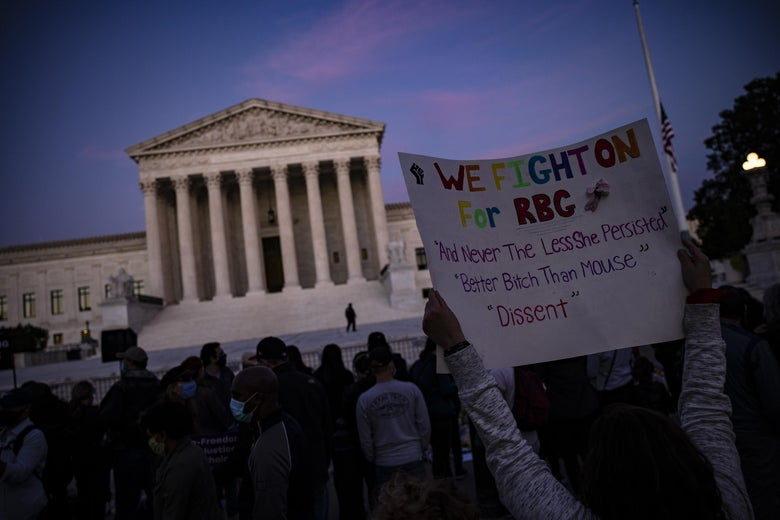 """A woman holds up a poster-board sign that says, """"We fight on for RBG."""""""