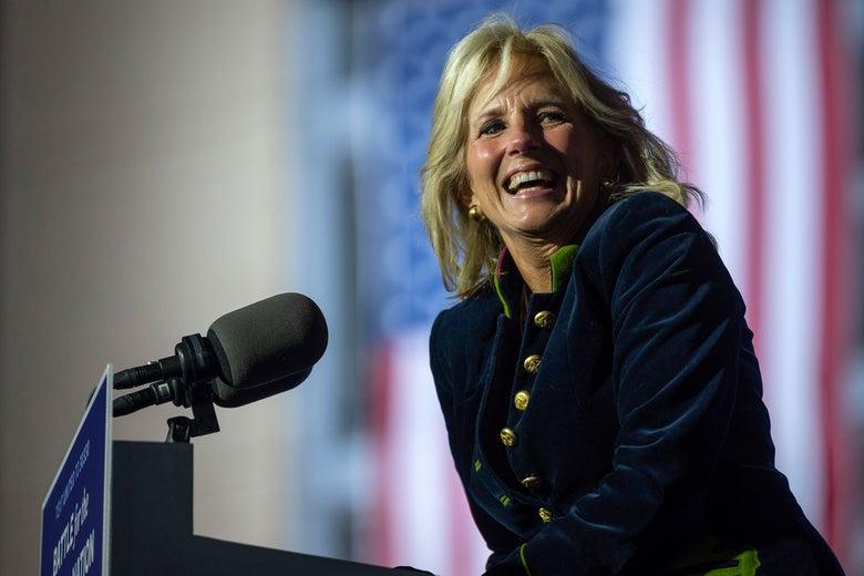 Jill Biden stands at a podium, grinning