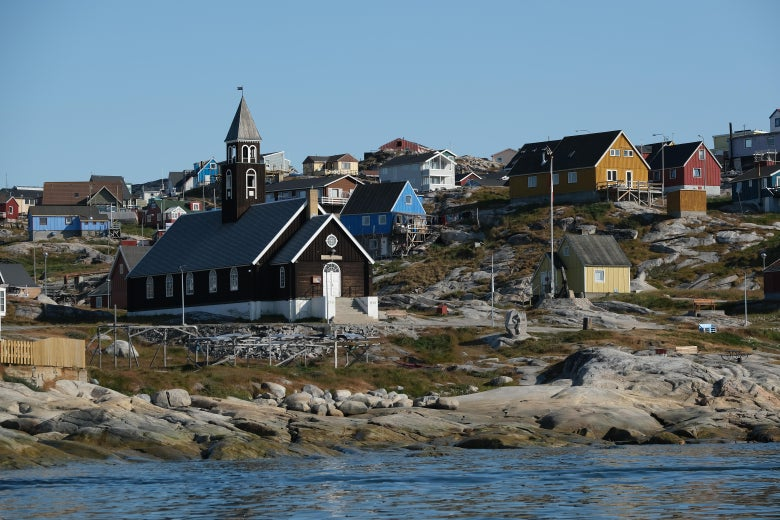 A church and a cluster of colorful buildings near a rocky beach.