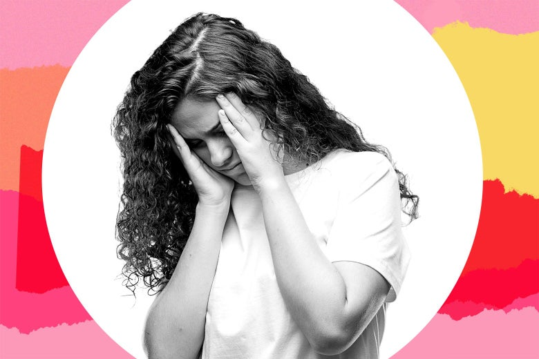A teenager holding her head, looking upset