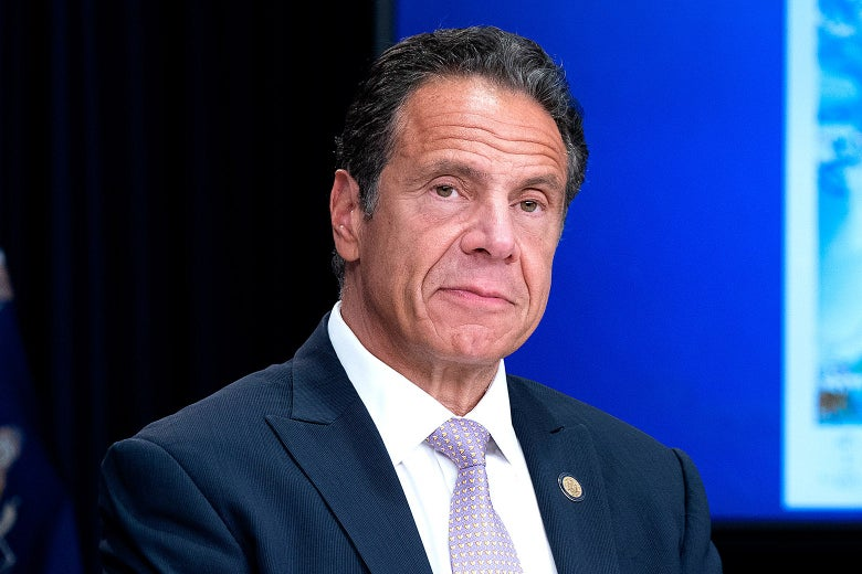 New York State Governor Andrew Cuomo sitting at a table with a serious expression while holding a media briefing.