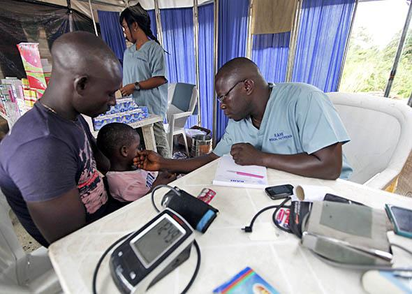 A doctor attends to a child at a relief centre for flood victims.