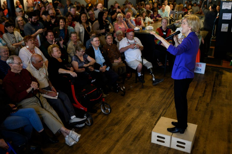 Warren, standing on wooden boxes and wearing a purple jacket, addresses a crowd of roughly 100 people.