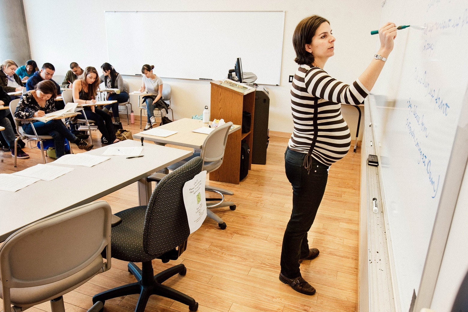 Rebecca writes on a whiteboard in front of a classroom of students.