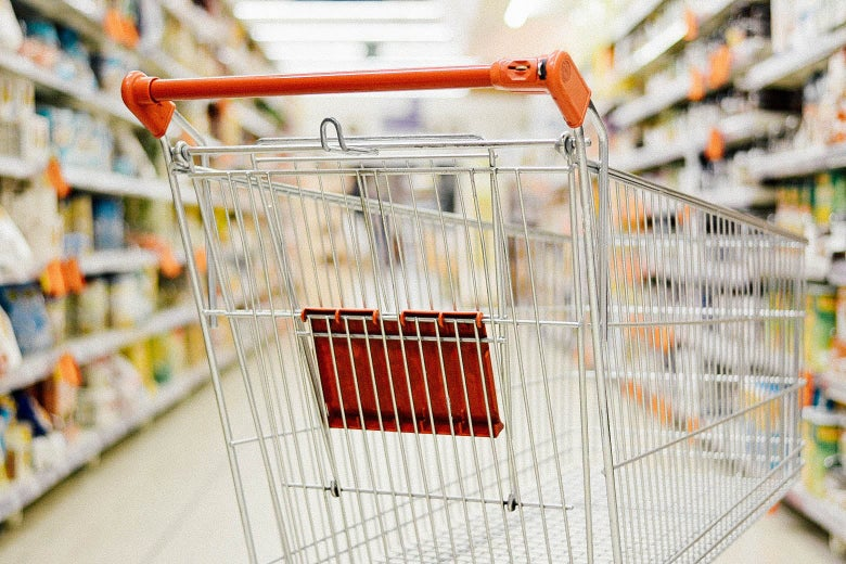 An empty shopping cart is seen in a supermarket aisle.