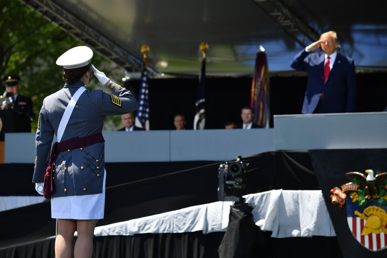 A female cadet with her back to the camera salutes Trump, who is standing on stage.