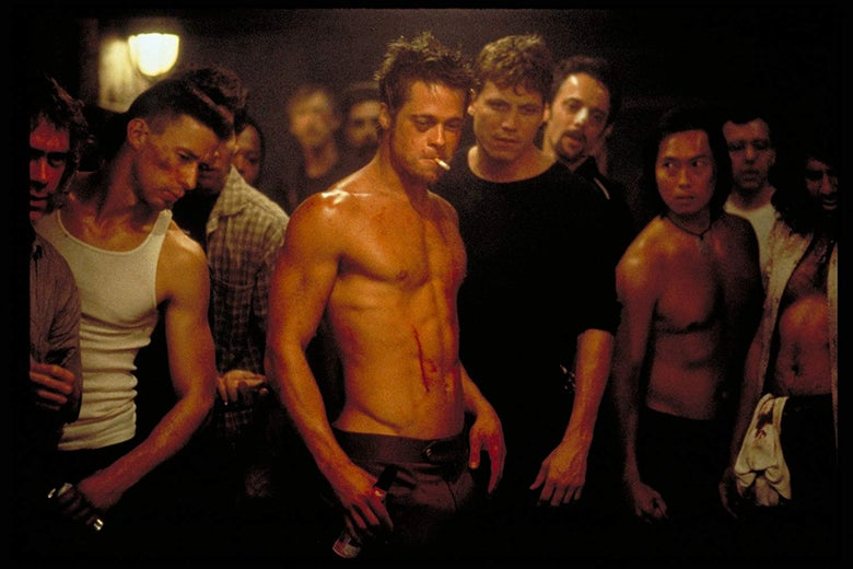 Brad Pitt stands shirtless in a crowd of bruised and bloodied men. A cigarette dangles between his lips.