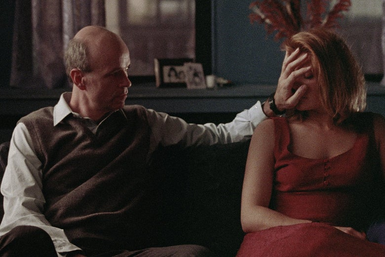 A man and a woman sit on a couch. The man places his hand over the woman's face.