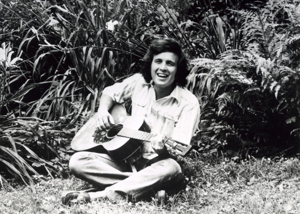 Don McLean smiling, holding a guitar, sitting on grass.