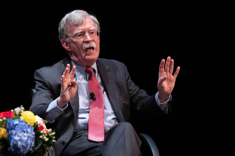 Bolton speaks on stage with his hands raised to head level.