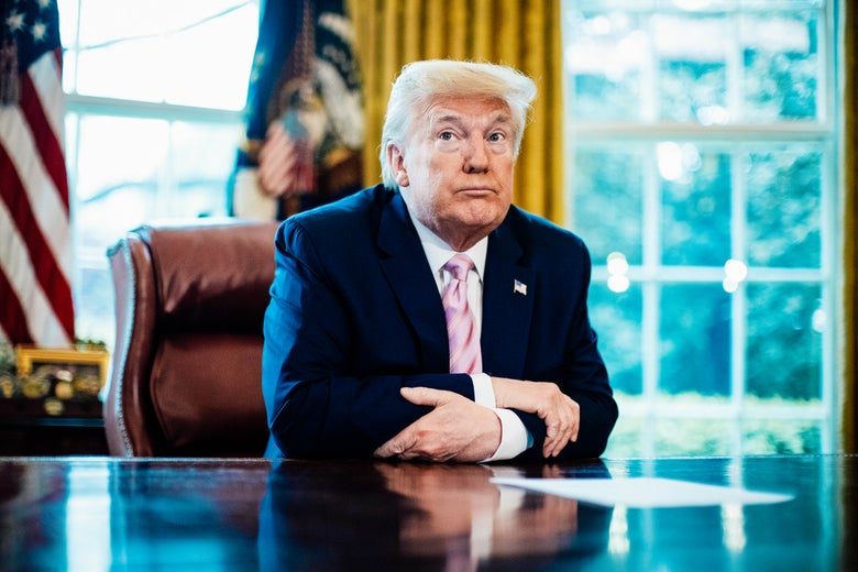 Donald Trump rests his crossed forearms on the desk in the Oval Office.