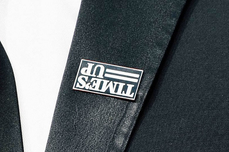 An upside down Time's Up pin on the lapel of a suit jacket.