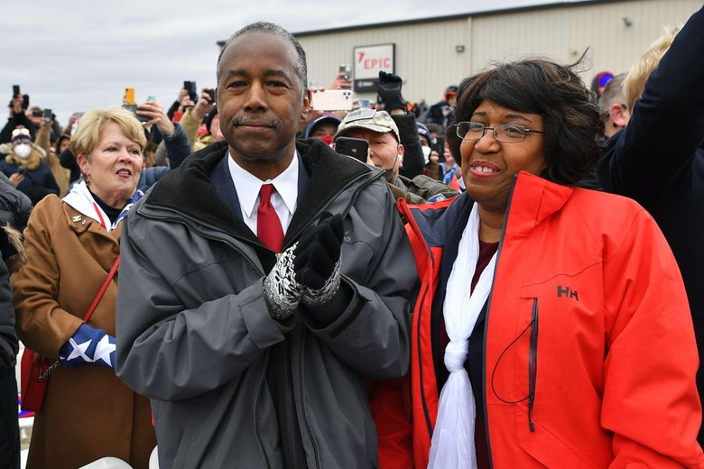 Secretary of Housing and Urban Development Ben Carson (C), with his wife Candy Carson (R), applauds as President Donald Trump arrives to speak at a rally at Oakland County International Airport, on October 30, 2020, in Waterford Township, Michigan.