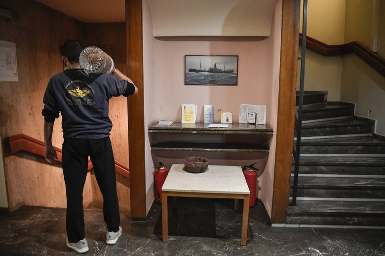 A resident of the Hotel Ionis carries water for the TV and coffee room at the hotel in the centre of Athens on October 22, 2020.