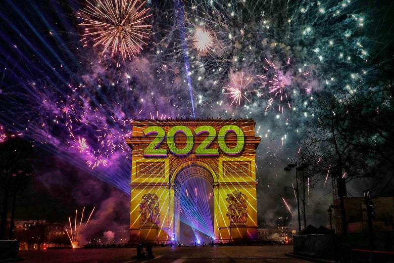 "Fireworks go off and ""2020"" is projected onto the Arc de Triomphe in Paris during the New Year's celebration."