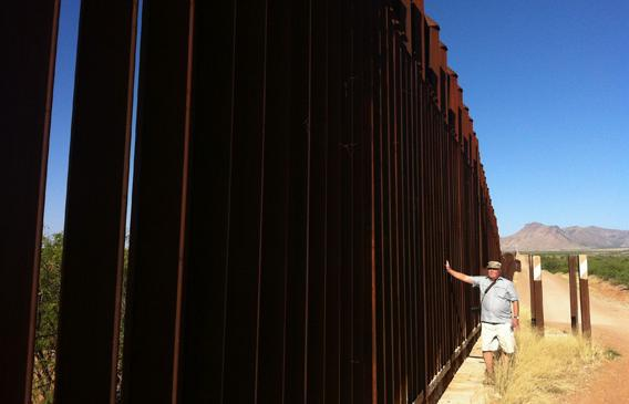 Glenn Spencer of American Border Patrol stands along the section of fencing right in front of his 104-acre compound.
